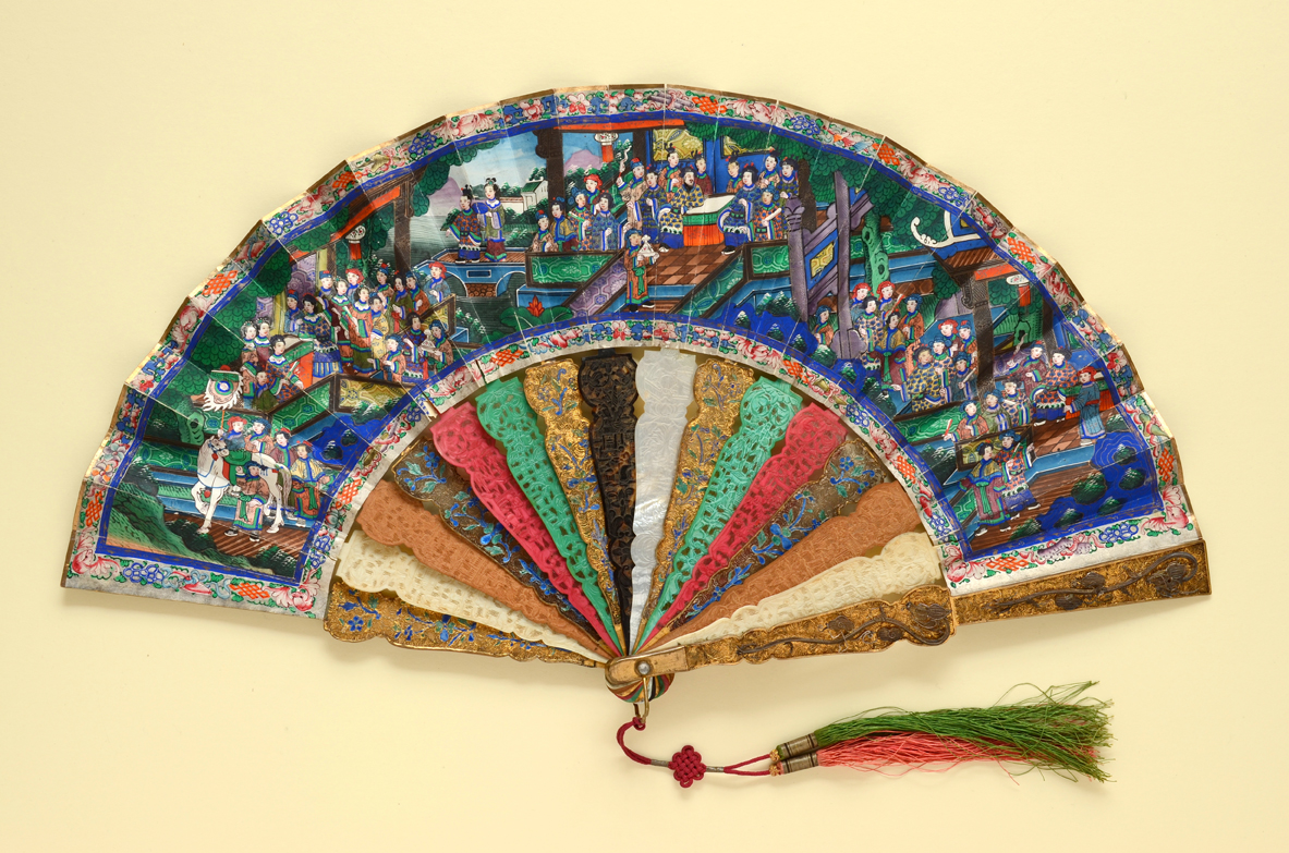 . 'Applied Faces' folding fan with lavish sticks of alternating materials. The double paper leaf is painted similarly on both sides with bustling scenes populated by Chinese officials and other figures with ivory faces and robes fashioned from fragments of silk.  Chinese (for export), ca.1880s The Fan Museum, LDFAN1990.1.1